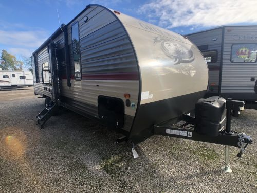 Door side exterior view of the Grey Wolf 26RR toy hauler travel trailer.